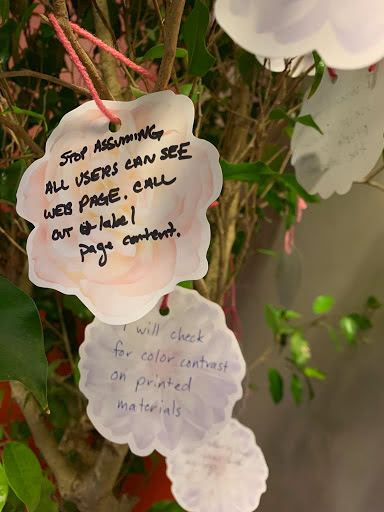 Several reflections written on paper flowers and hung from a branch on the tree.