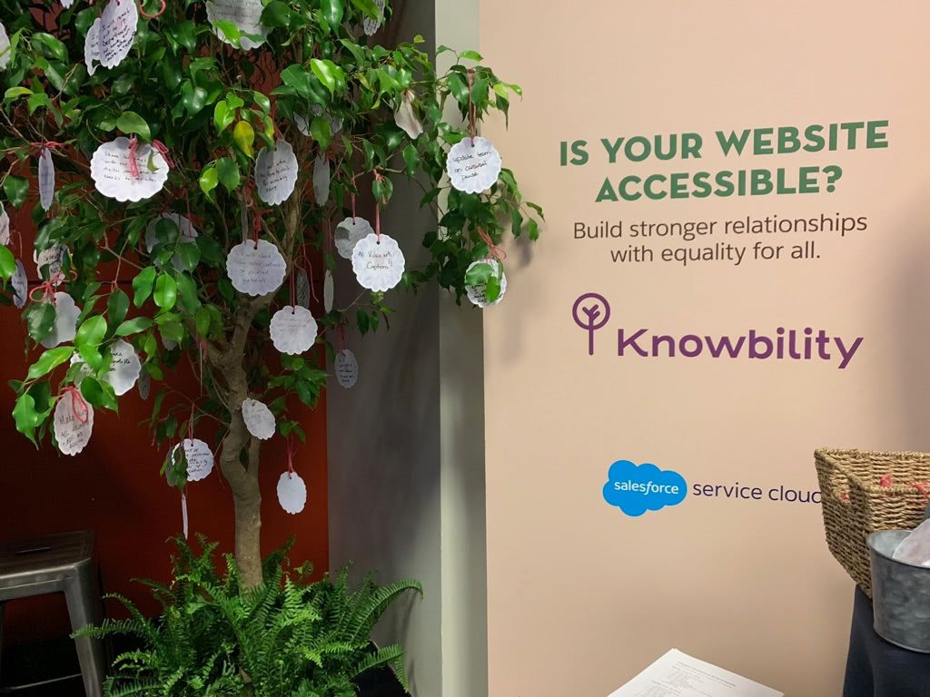 Photo from event showing Knowbility and Salesforce poster as well as a tree with written reflections on small paper flowers hanging from the branches.