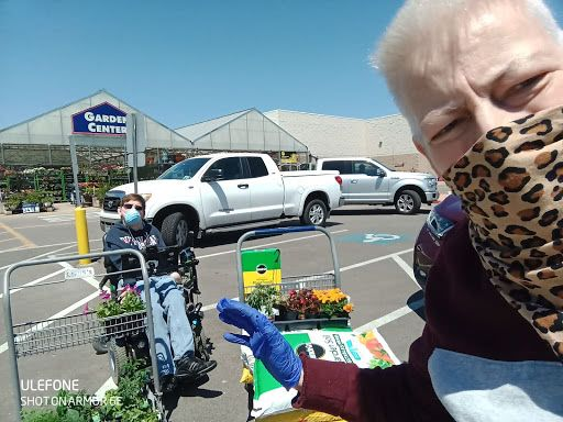 person wearing a cloth face mask standing in the parking lot of a garden center next to shopping carts full of plants