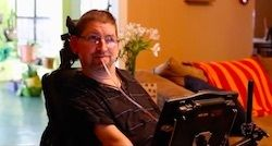 Dave Chapple in wheelchair using a sip and puff assistive technology device
