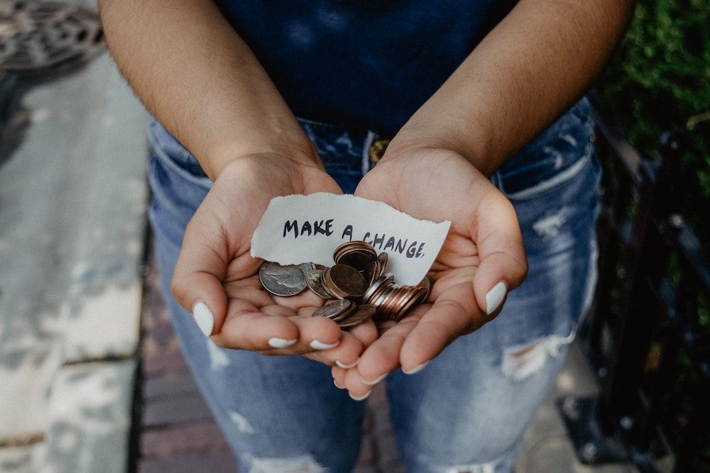 Person's cupped hands holding coin change with a note that says make a change