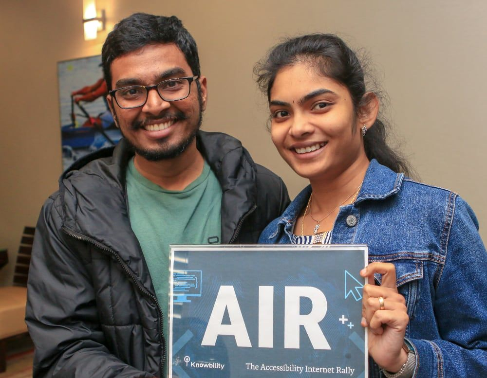 Two young people holding an AIR sign.