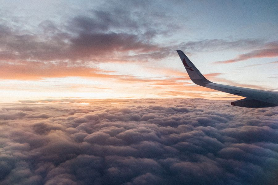 Image of an airplane wing flying over clouds with a sunset in the background