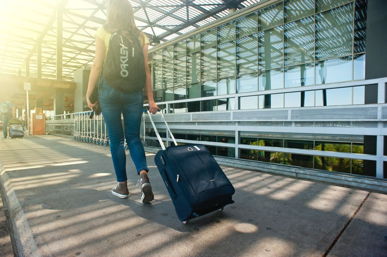 A woman walking through an airport pulling a wheeled suitcase