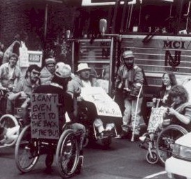 "Archival photograph from Smithsonian exhibit on the history of the ADA. Veterans in wheelchairs gathered at a bus station. One has a sign on the back saying ""I can't even get to the back of the bus"""